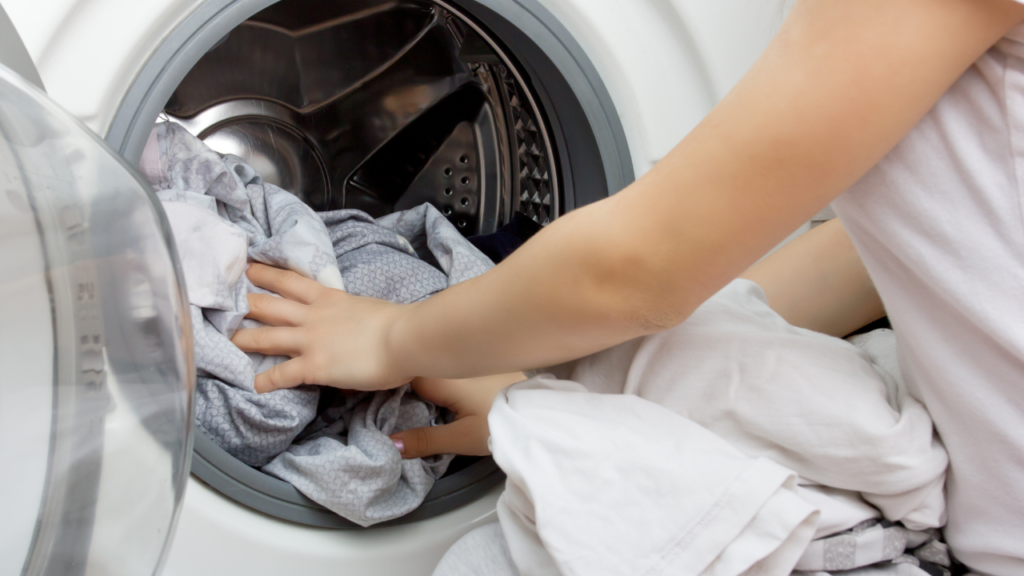 Woman taking laundry out of an impeller washing machine