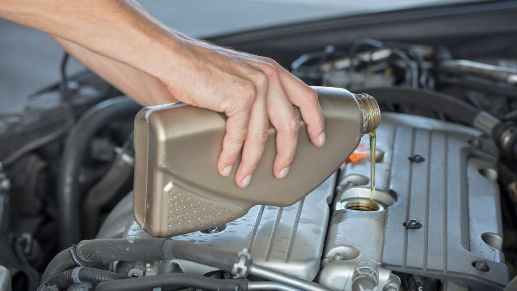 Man pouring a bottle of conventional oil to the engine