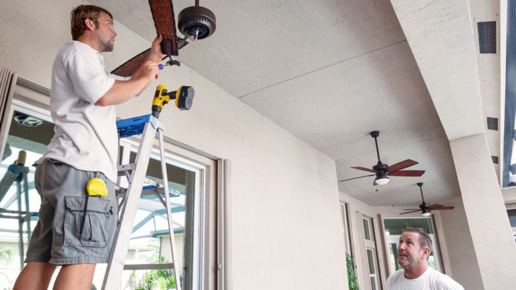 Man installing the support brace and u-bolt of ceiling fan