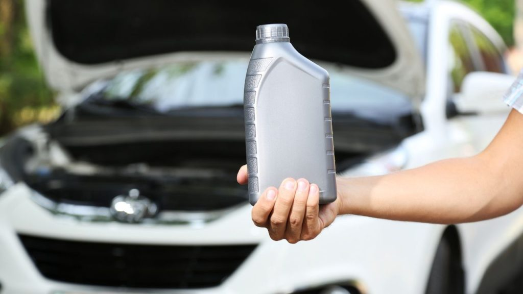 Man holding a bottle of synthetic oil