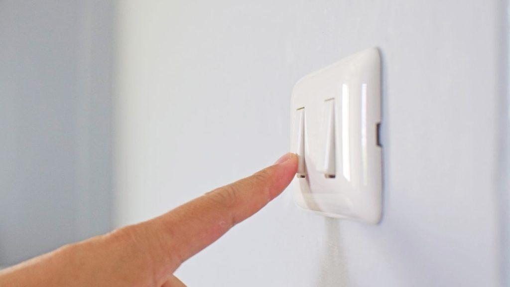 Women pressing switch ceiling fan button