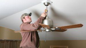 man installing a ceiling fan